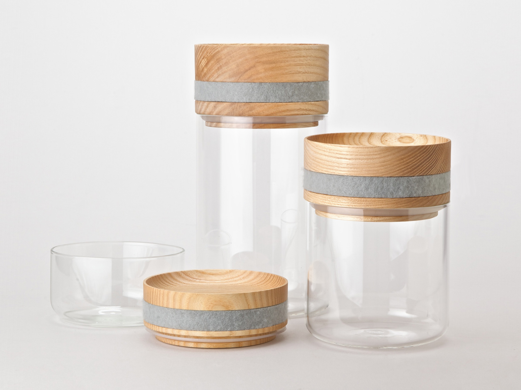 Obtineo minimal storage containers made from glass, ash and grey felt