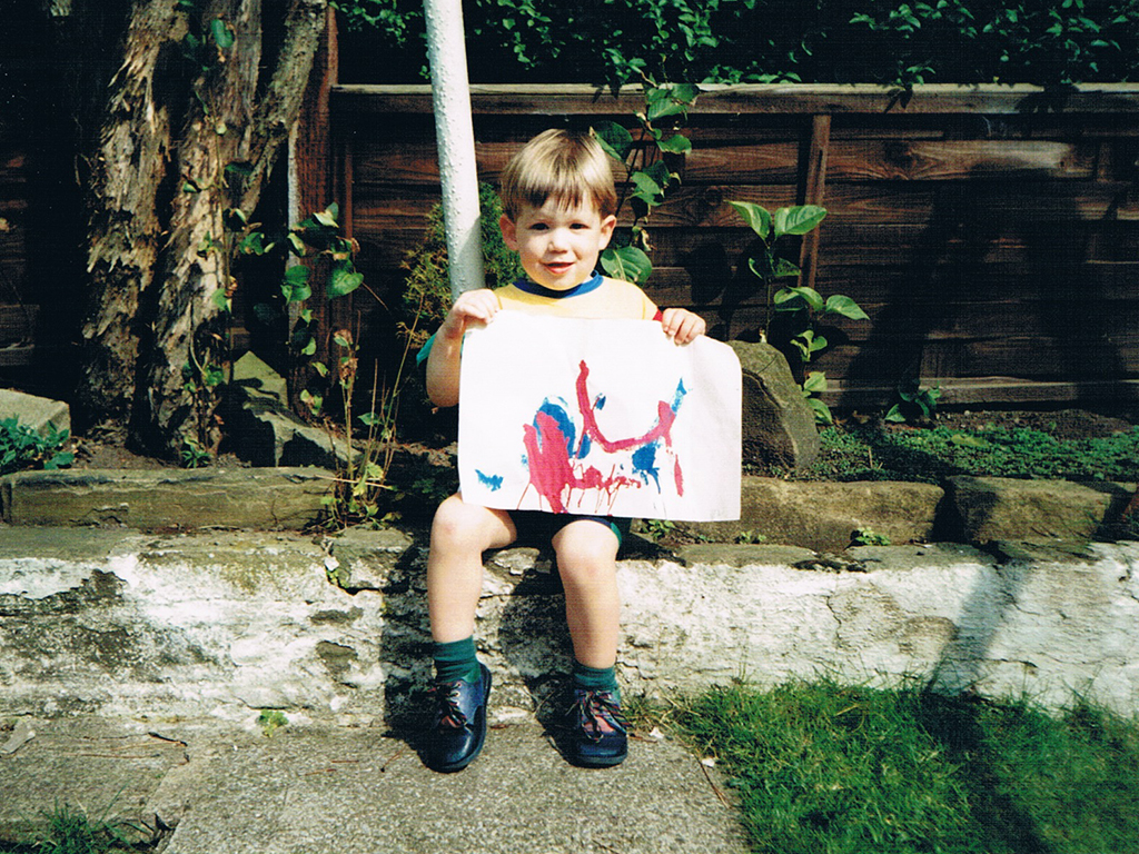 Tom Hutchinson holding painting as a small child in the back garden